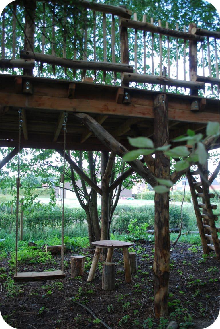 Terras op hoogte met schommel onder en boomstronk krukjes
