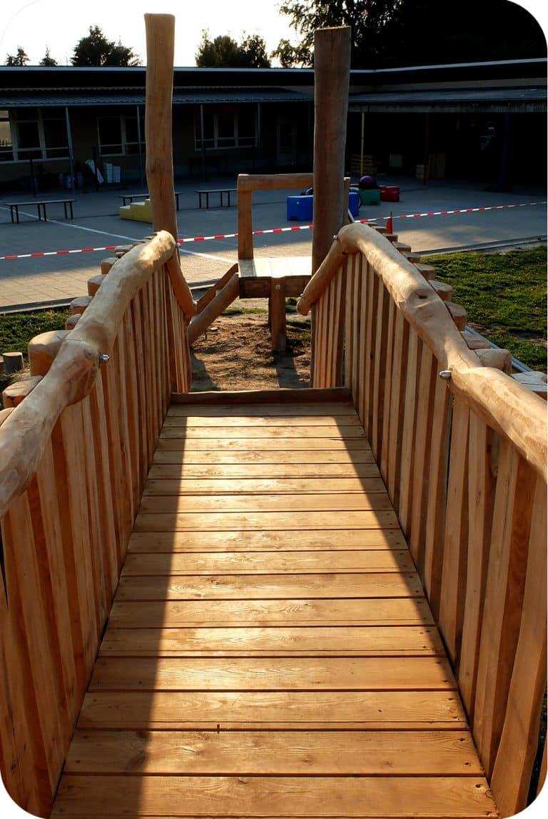 Houten loopbrug op de speelplaats 'de bron'
