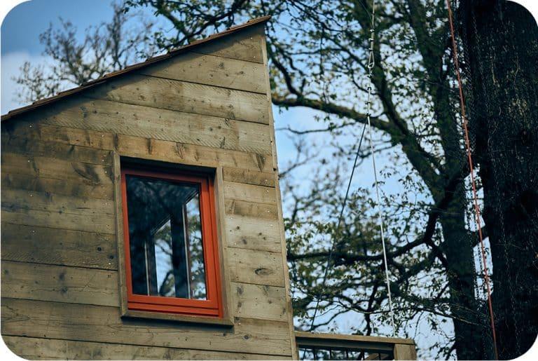 Boomhut bouwen in steigerhout met dak in red western cedar shingles en oranje ramen